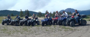 A team of ATV riders pose on a mountaintop during Father Teen Adventure.